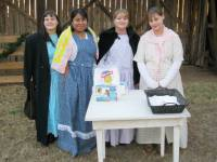4 yound women in pioneer dress behind the refreshment table
