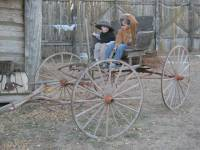Two children sitting on an old buggy