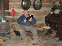 Man reading Bible inside Smith Log Cabin