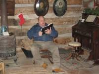 Man reading Bible inside Smith Log Cabin