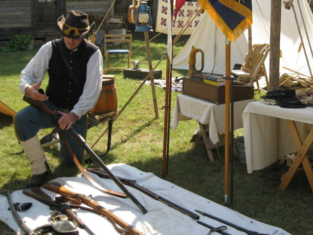 man showing historic rifles