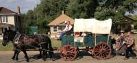 covered wagon pulled by horses with people walking behind it