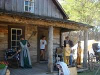 People in front of the 1877 2-story log cabin