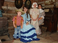 Two women and two children in period dress inside the log cabin